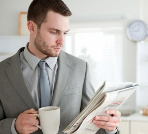 Businessman drinking coffee while reading the news
