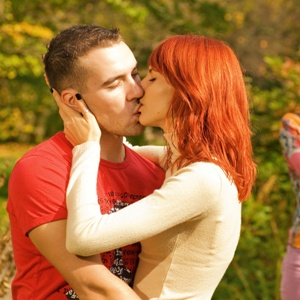 Young couple kissing and offended girl standing on a background (shallow Dof, focus on couple)