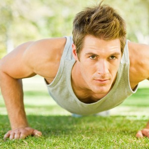 Physically fit boy doing push-ups at the park