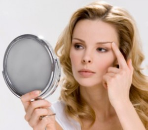 Young woman looking at reflection in hand mirror, touching eyebrow