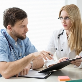 Two young experienced doctors diagnosing the patient