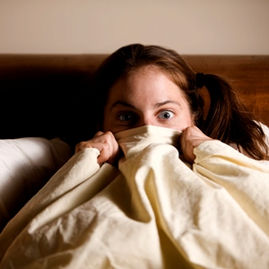 Frightened Woman in Bed with the Sheets Pulled Up to her Face