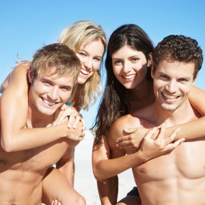 Two couples piggy back riding at the beach